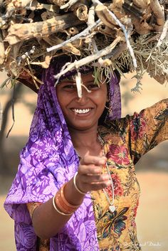 Portrait of a young Rajasthani girl carrying firewood on her head, India - by  DocBudie