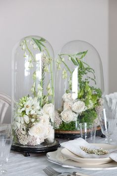 Perhaps cloches, with a single cherry blossom sprig, or fern frond, in the tablescape for round tables