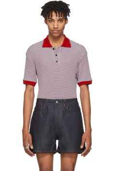 Short sleeve knit cotton polo shirt striped in tones of red, white, and blue. Spread collar and cuffs in red. Three-button placket at front. Vented side-seams. Tonal stitching.