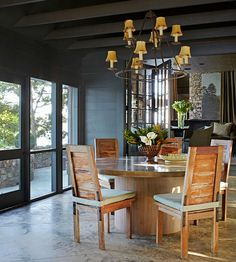 Dark wood-plank walls and exposed ceiling beams create a dramatic style statement in this casual dining room. The warm wood finish on the chairs and dining-table base ensure the space doesn't look too dark. The concrete table