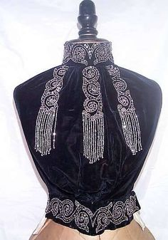 Beaded velvet dickie or vest ca. 1900. Would have been worn under a jacket or short bolero jacket for a special occasion. Silk velvet with heavy steel seed beads and sequins. including hanging fringes. Back is of sturdy cotton and fastens with linen covered buttons and a drawstring at the waist.