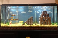 Michigan-based ad copywriter Cedrick Bearss recreated the iconic first level scene from Super Mario Bros inside his 55 gallon fish tank. Almost everything, including Mario, was made of LEGO bricks. Lego Super Mario, Super Mario Bros, Mario Bros., Lego Mario, Diy Aquarium, Wall Aquarium, Aquarium Rocks, Aquarium Stand, Aquarium Setup
