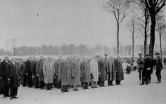 Newly arrived prisoners, still in their civilian clothes, and after shaving and disinfection, stand at roll call in Buchenwald concentration...