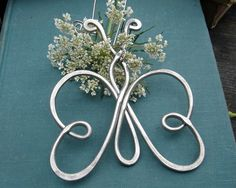 This playful butterfly is handmade with 9 gauge aluminum wire that we hammered for extra strength. Aluminum makes it much lighter than it appears! The hook is handmade from stainless steel wire. The widest part across the wings are about 2 7/8 - 3 1/8(7.4-8.cm). The butterfly measures about 3 1/2-3 3/4(8.9-9.5cm) long from the top of its antenna to the bottom of its wings. It entire piece measures about 4 3/4 (12.2 cm) from the top of the hook to the bottom of the tail. This could be an…