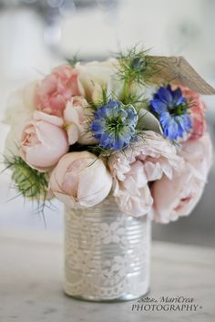 a tin can, covered in lace, with bouquet of wild-looking flowers. Simple to pull together but perfect for a centerpiece in no time.