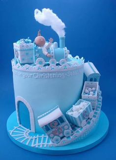 cake decoration ... baby cake in pastel blue ... little train cars spiral around the outside to reach the top ... adorable!!!