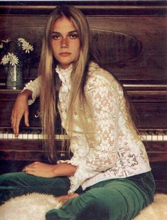 Peggy Lipton. Forest green velvet pants. Lace turtleneck shirt. button sleeve. daises. piano. very 1960s early 1970s