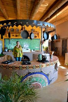 U-shaped kitchen. Multiple stove tops, shelving underneath with ovens on open ends. Dreamcatcher, Arkansas Earthship