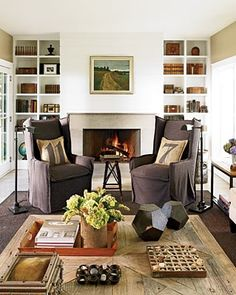 Traditional Vacation Home with a Modern Twist: The fireplace surround in the living room is faced with micro-hammered limestone; shelves hold vintage books, lap desks, and other collectibles.