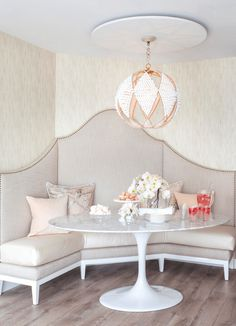 Banquette, marble table, and light fixture from Peridot Decorative Homewear.