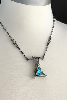 A beautiful piece of rainbow laminated optical & dichroic glass, cold worked faceted layers, one of a kind, oxidized sterling silver, custom chain, sculptural necklace The setting is oxidized sterling silver, with custom chain. The chain is 16 long, and has a shepherd hook clasp, so
