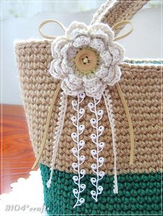 crochet flower, button center, ribbon strings.  (perfect for kiddos hats)