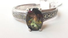 Ameriston presents a bi-color tourmaline solitaire ring, handmade and self-set. The center stone is a natural bi-color tourmaline with marcasite accents. The stone is more a tri-color tourmaline with three shades with green, brown and pink. The metal is sterling silver with a 925 stamp on the inside of the band. The Tourmaline has both green and pink shades. The stone has inclusions.    All Measurements Are Approximate Due To The Handmade Nature Of This Ring.    Stone Cut: Faceted Emerald…