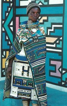 Ndebele woman standing in front of a traditionally painted Ndebele home. South Africa