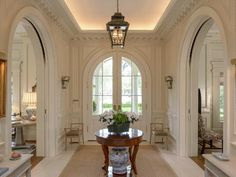 Beautiful white entry way heavy trim and panelling, half french curved doors, white floors