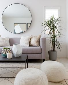 Neutral living room decor with clean lines and lots of texture // round mirror // Grey fabric sofa // rope poufs // From @homepolish.