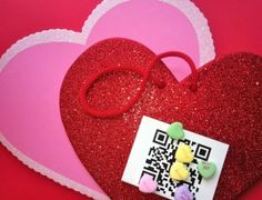 Image of heart shaped candies, sparkling valentines and a QR code