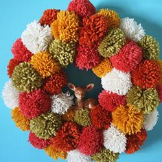 Puffy Pom-Pom Wreath  Create this adorable wreath featuring yarn in all your favorite fall colors. Just start with a straw wreath, wrap a base fabric around it, then tie the pom-poms on until your wreath is full.