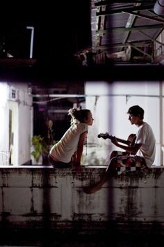 Young man playing guitar for a young woman