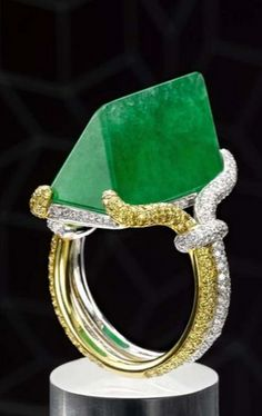 A polished rock of green jadeite, set in a yellow and white gold ring by Samuel Kung.
