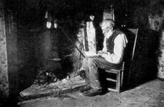 Old photograph of a Crofter reading by the fire in his cottage on Isle of Skye, Scotland.