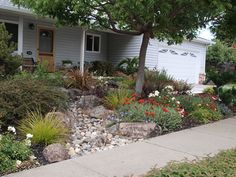 River rock and boulders through garden to sidewalk