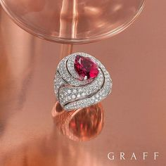 Graff Diamonds. A swirl of diamonds presents a stunning 3.94ct pear shape pink sapphire in this cocktail ring, new from the workshop.