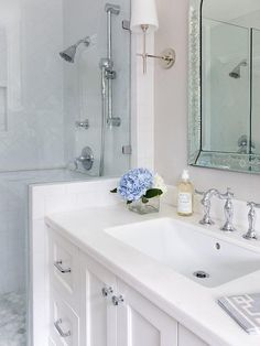 Gorgeous bathroom features a glass enclosed walk in shower accented with white herringbone shower tiles framed by white subway wall tiles lined with marble pencil tiles highlighting the white herringbone upper wall tiles framing a tiled niche.