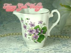 """Take a look at this lovely little creamer pitcher in fine bone china created by Royal Grafton of England. In excellent condition this pretty pitcher features a beautiful design of blooming violets on both sides. Measuring in at 3-1/8"""" tall and 3-3/4"""" wide (including handle and spout), this vintage creamer also has gold detailing on the rim and at the handle. what a fine addition this elegant creamer would make to your breakfast or tea table!    *** You can now feel even better about shopping…"""