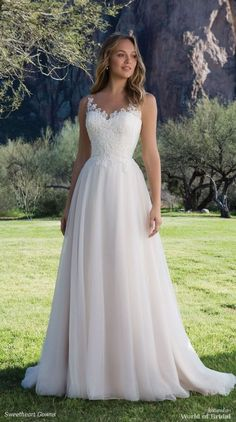 Embroidered lace adorns the Sabrina neckline and bodice of this light wedding dress. Layers of tulle create a full skirt that is fun to wear.