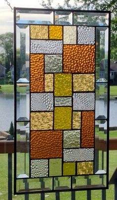 This stained glass panel is sampling of shades and textures of glass in a geometric abstract pattern in amber and clear. The panel is approximately 19