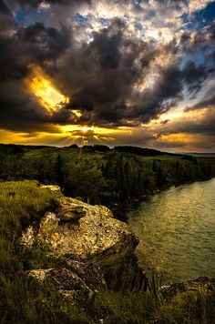 The sun sets on the Bow River, and Fish Rock on Sentry hill, near Cochrane, Alberta, Canada