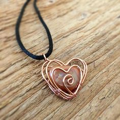 "This necklace features a copper, wire wrapped heart cage with handpicked agate inside. Copper heart is 20 gauge wire and woven together using 28 gauge copper wire. Charm measures 1"" in length on a black satin cord that measures 22"" in length. Satin cord is fastened with a silver"