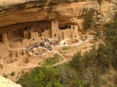A wider view of the Cliff Palace at Mesa Verde with a tour group gathered on the terrace.