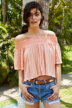Off the shoulder peach flowy shirt with denim shorts and brown buckle belt