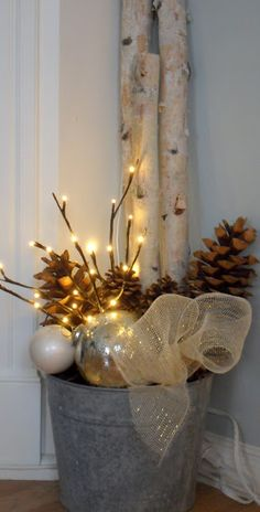 lighted branches and pine cones in galvanized bucket