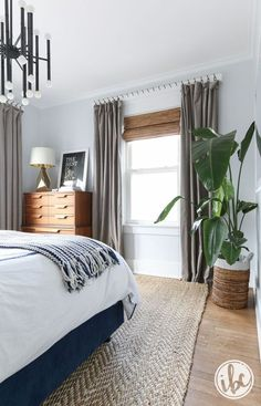 gray, white, wood, and neutral bedroom - love all the natural light, wood floors, white bedding, and funky light fixture