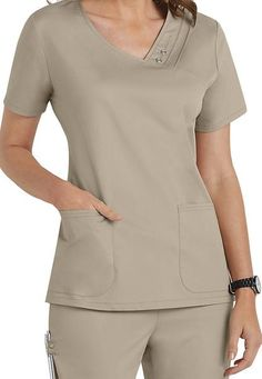 An asymmetrical V-neck top features multiple pin-tucks, tonal snaps and zig zag stitching. Release darts at back waist, front curved patch pockets, and side vents complete the picture. Center back measures Poly Rayon Spandex Twill Cute Nursing Scrubs, Cute Scrubs, Scrubs Outfit, Scrubs Uniform, Beauty Therapist Uniform, Scrubs Pattern, Stylish Scrubs, Beauty Uniforms, Uniform Design