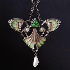 """1900-10.  Art Nouveau (Jugendstil) style.  Plique-a-jour enamel pendant, silver mount, with pearls & a green gemstone. Made by Hermann & Speck of Pforzheim, Germany  Pendant 1.7"""" wide x 1.6"""" tall (appx. 4.5 x 4 cm) from eBay eyedeal2, July 2014  Plique a jour is enamelling done in open spaces of the metal -- not to be confused with either champleve or cloisonne enamelling, which always have metal behind the enamel.  At its best, this jewelry looks like tiny stained-glass windows."""