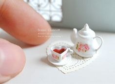 Miniature cup, saucer, and teapot. In 1:12 scale.