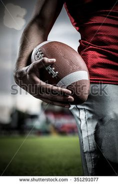 Cropped image of sportsman holding American football against pitch