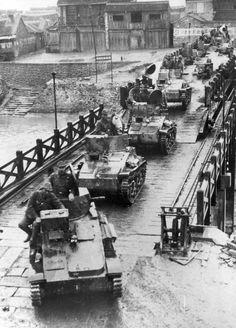 A convoy of Japanese light tanks crosses the bridge across the river.