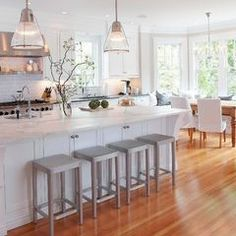 white cabinets, light countertops, wood floors, window seat with kitchen table