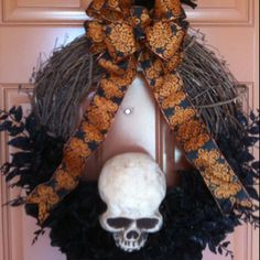 Halloween Wreath: I made this with a grapevine wreath, black glitter roses, black and orange ribbon, and a foam skull. What you cannot see us the black raven perched on top. All items were purchased at Michael's Craft Store.