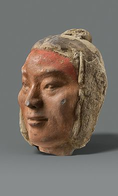 """This detailed visage of a young warrior is among the most striking to be recovered from the tomb of Emperor Jing (r. 157–141 B.C.). His well-modeled physical features perpetuate the """"realism"""" of Qin sculpture—represented most notably by the terracotta warriors of the First Emperor of Qin"""