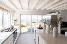 An all-white kitchen overlooking the beach is what dreams are made of. | 12 Gorgeous Kitchens That Will Make You Want To Redecorate