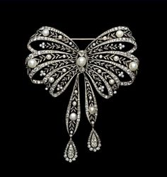 Platinum millegrain stomacher brooch in the form of a bowknot with diamond ribbons enclosing sprays of diamond leaves with natural pearl berries, meeting at a large centre button pearl within a navette shaped frame and terminating in twin pear-shaped diamonds swinging in diamond borders. Chaumet, Paris, c. 1900.