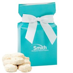 This brand new box will be sure to get you a standing ovation with your clients. Filled with the bakery items delight of almond tea cookies, you will gain rave reviews with this high-gloss box that includes your logo and a white bow. Great corporate food gift for the holidays and Christmas.