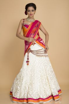 Wedding season is here, buy this tastefully done white lehenga with a flame  orange blouse with a fuchsia yoke, sweetheart neckline blouse. This is adorned with embroidered patterns, crystals with bugle beads and faux pearl. It panels around the hips which is quite appealing, fuchsia and orange panel at the border and a matching dupatta. Blouse again is embellished with faux pearls and bugle beads with a dori with tassels at the back.