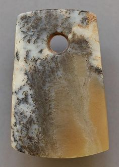 Jade. Late Neolithic period, early Bronze Age, c.2100-1900 BC <br> ??? - ?????, ???21??-?19?? <br> ? 8,3 ??; ? 5,4 ?? <br>  <br> The most striking feature of this roughly rectangular shaped jade axe is the multicoloured type of jade out of which the object has been carved. One portion of the blade is in fact of a yellowish, opaque colour which contrasts pleasantly with the snow-white hue on the sides of the axe. The white areas are also crossed by numerous, short black veins generated by the…